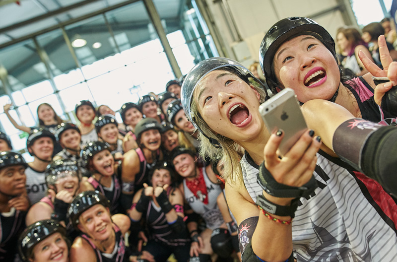 Shortstop, Gotham Girls Roller Derby and Shaolynn Scarlett, London Rollergirls, take a joint selfie with their teams